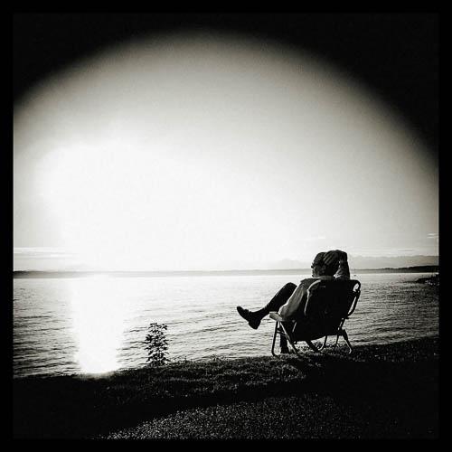 En ensom mann nyter en varm høstsol ved Elliot Bay Marina