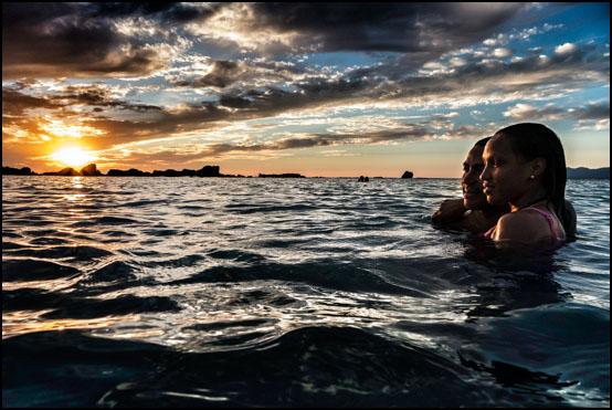 Et forelsket par nyter den vakre solnedgangen ved Playa Anchon